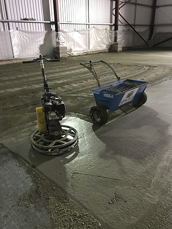 5. The topping spreader is used to incorporate the dry shake topping into the surface of the concrete evenly.