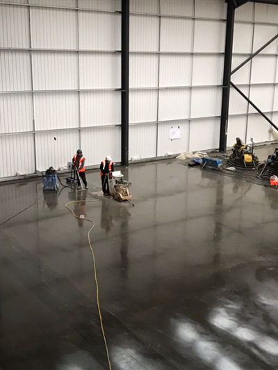 The above photograph shows a warehouse concrete floor in Reading, Berkshire, with a natural dry shake surface hardener integrated within the surface of the concrete to increase the amount of abrasion resistance of the concrete under heavy trafficking.