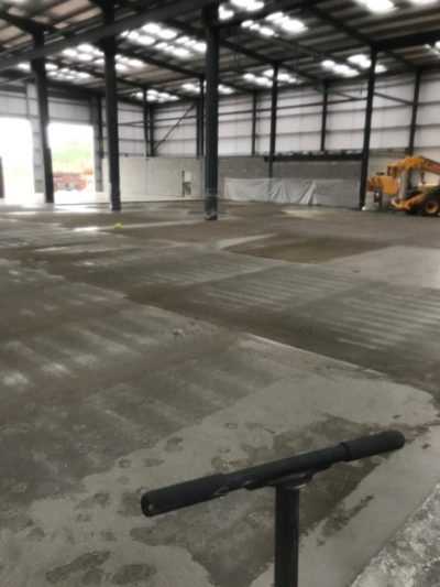 Dry shake topping evenly spread via the topping spreader to the concrete surface prior to being powerfloated and polished