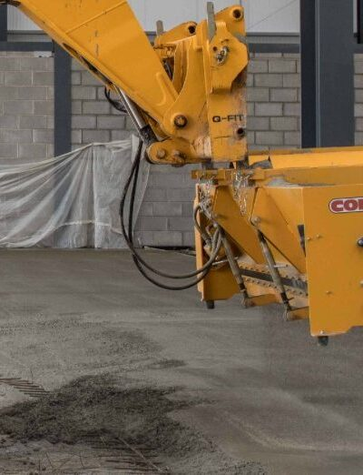 Dry shake surface hardener and topping applied to surface of the fresh concrete using a mechanical topping spreader.