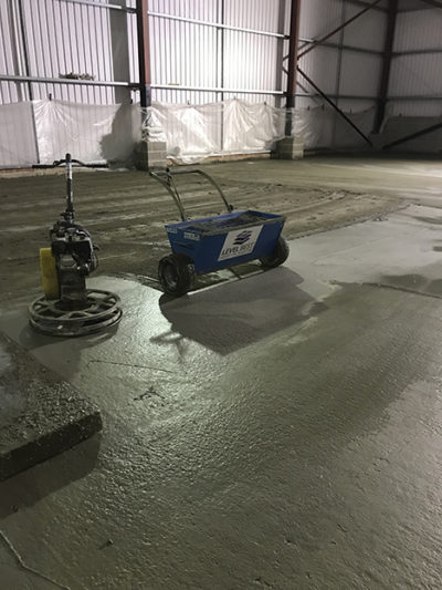 Dry shake topping applied to the surface of the concrete using a topping spreader.